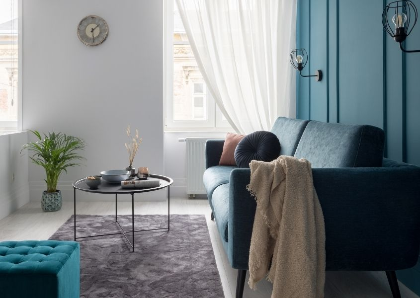 Narrow living room with blue painted wall and grey sofa