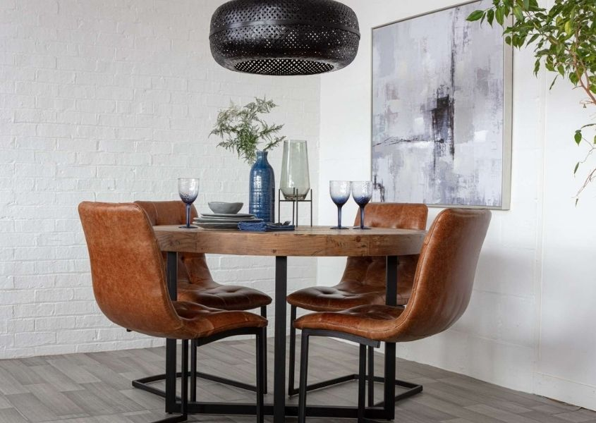 Round industrial dining table with tan leather dining chairs