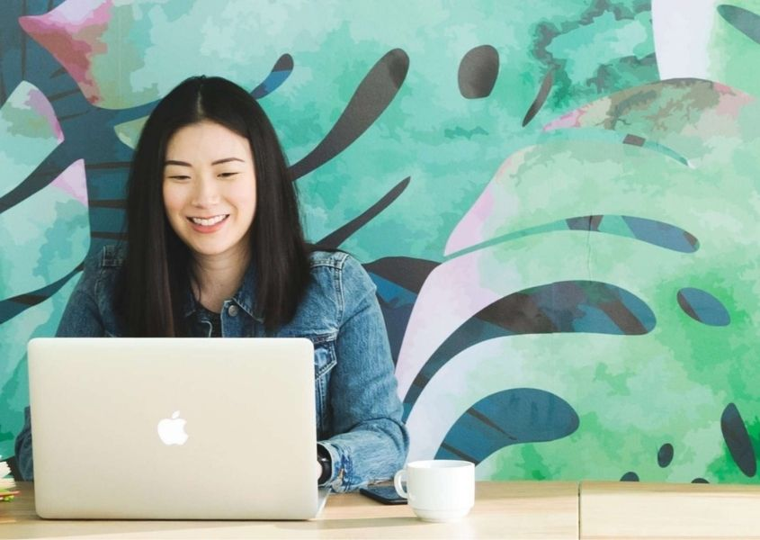 woman sat at desk with large green palm mural on wall behind