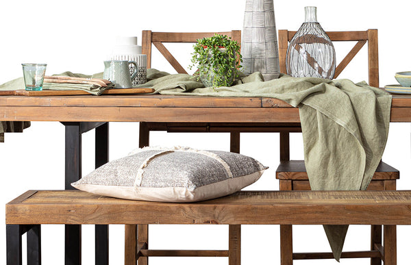 Rustic wood dining table on black steel legs with light green table linen, a grey pillow and ceramics