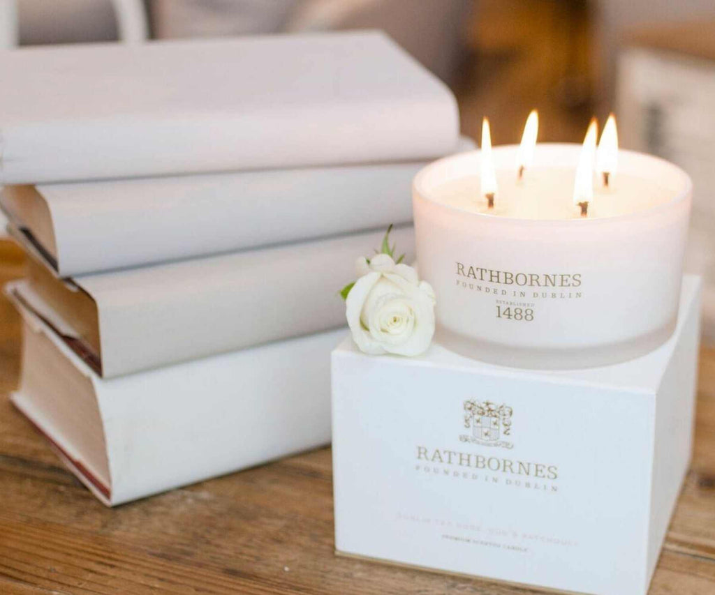 White scented candle next to pile of white books on wooden table