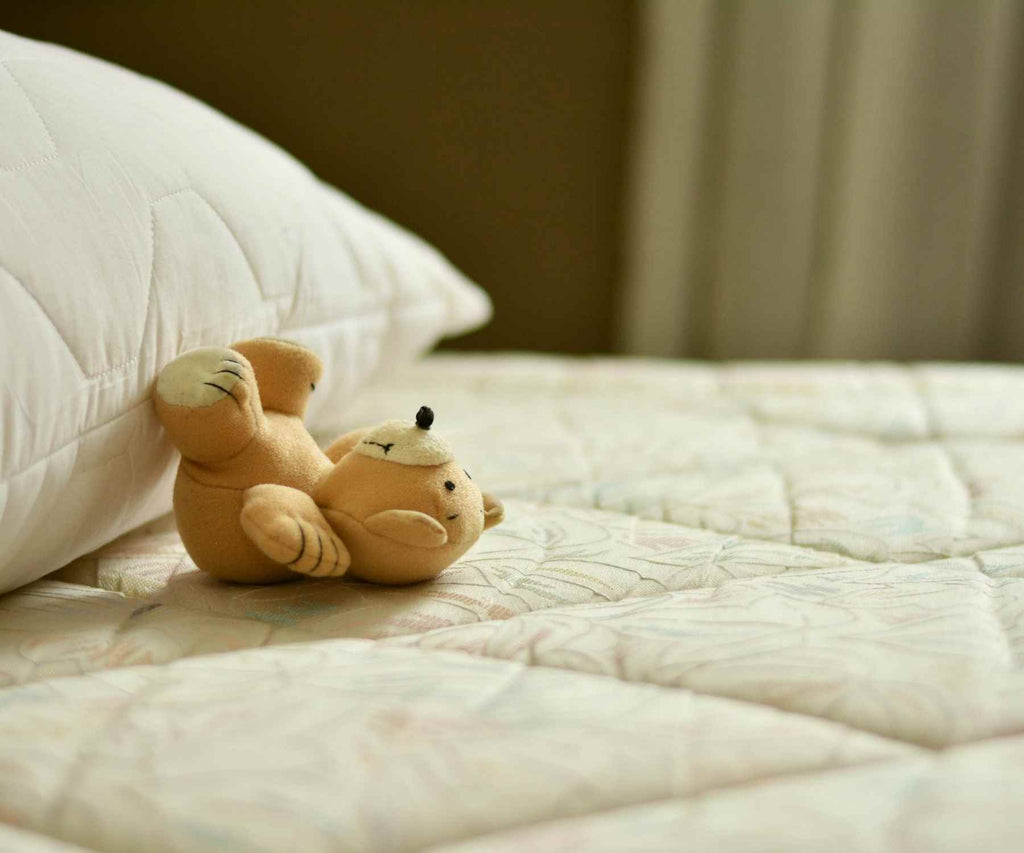 Close up of mattress with small teddy bear and pillow