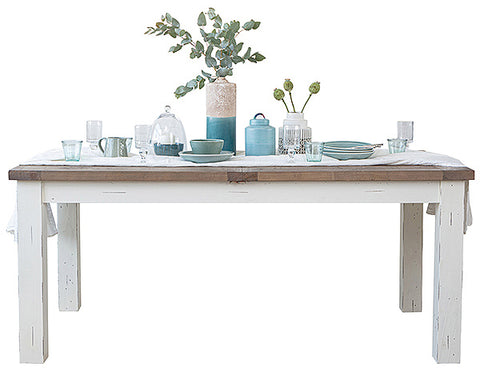 White painted wooden dining table with decorative items placed on top