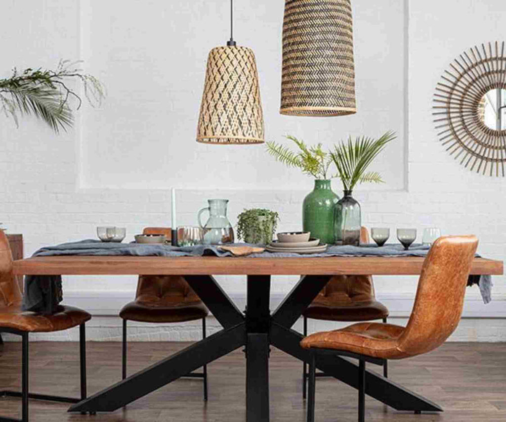 Tapered bamboo pendant lights over wooden table with black spider legs and brown faux leather chairs