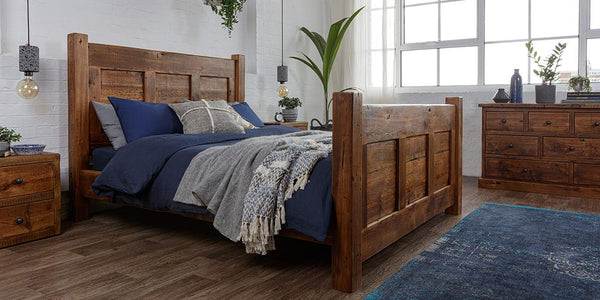 A reclaimed wooden bed in a bedroom with matching bedside tables, a blue rug and chest of drawers