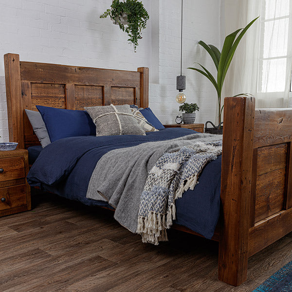 Dark reclaimed beam bed and bedside table, with navy blue and grey duvet covers and blankets and greenery