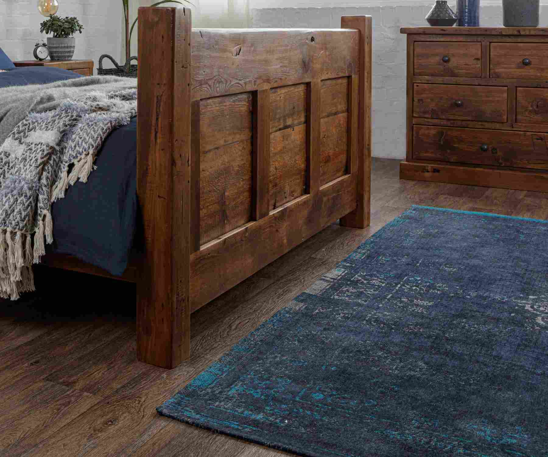 Reclaimed wood bed and blue rug