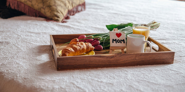 A wooden tray with a croissant and flowers on top of a bed