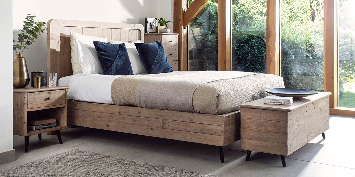 Reclaimed wooden blanket box in front of a matching wooden bed