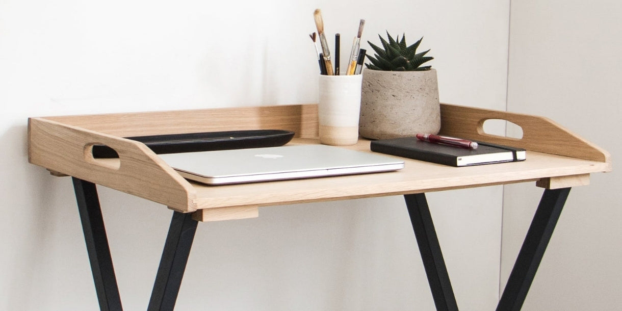 Life style photograph of wooden tray-style writing desk, styled with laptop and stationary.