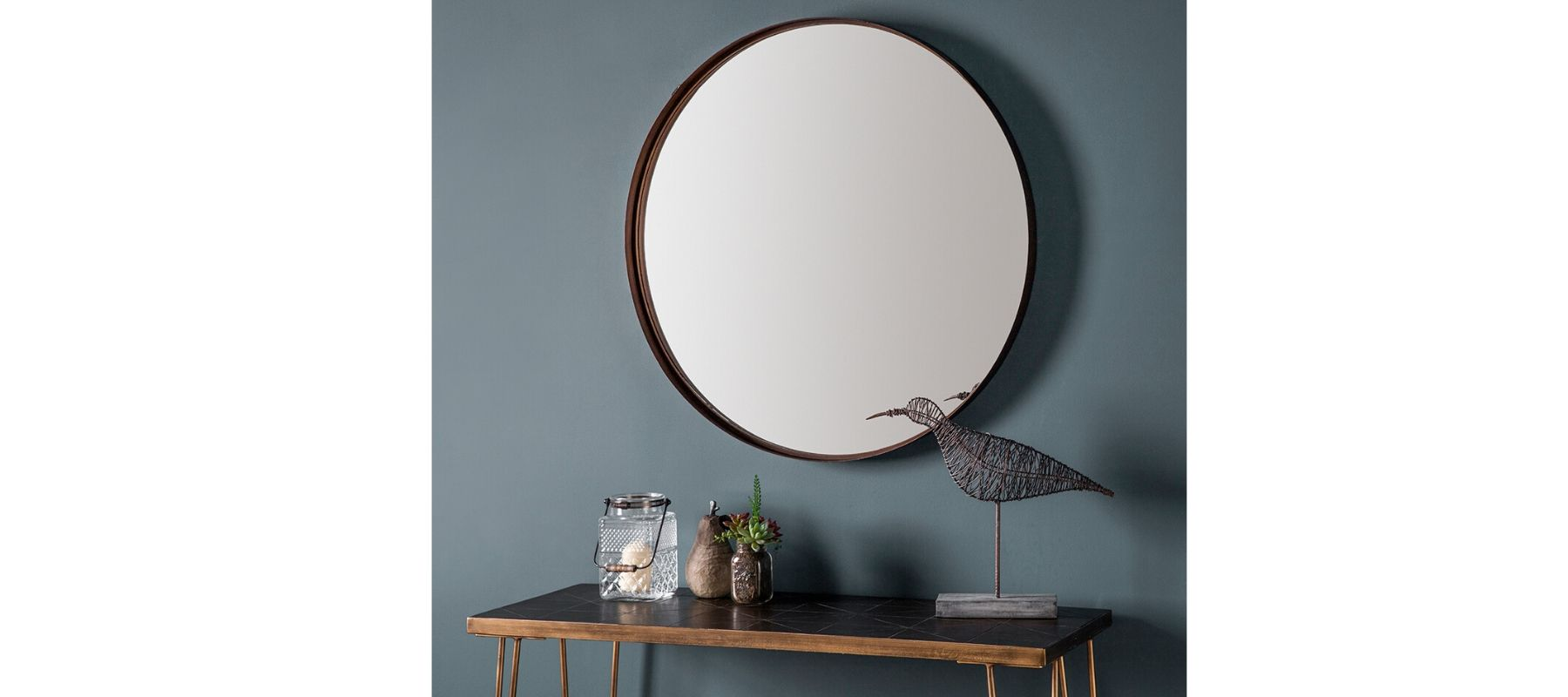 Round wall mirror on blue wall above a console table