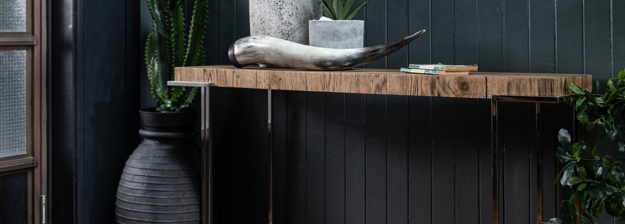 A decorative horn sits with plants on top of the Knightsbridge Reclaimed Oak Console Table