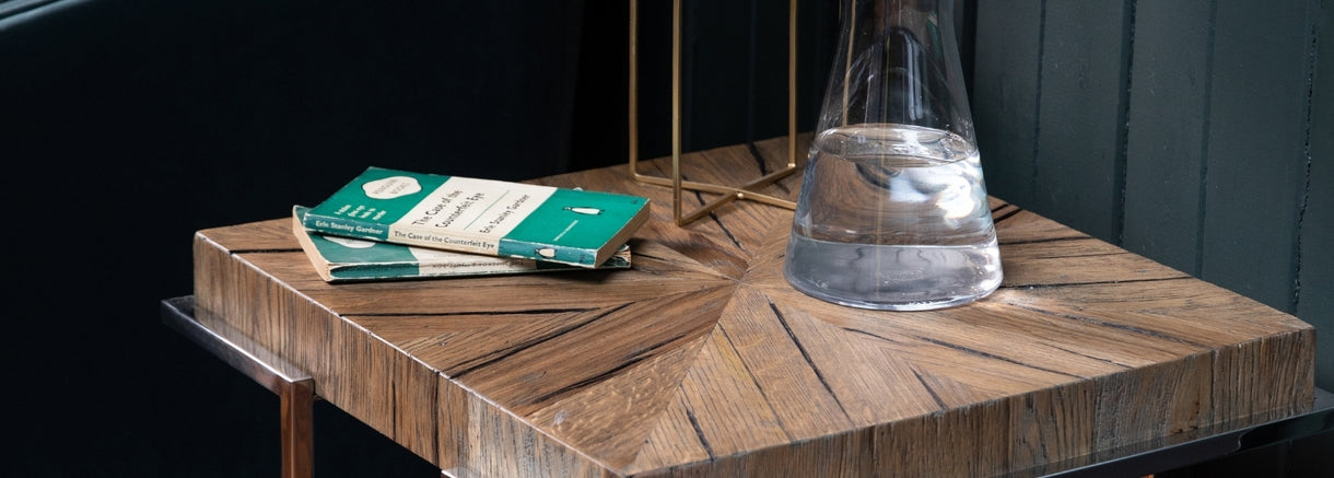 The Cotswold Reclaimed Oak Lamp Table, shown here with books and a water jug resting on it