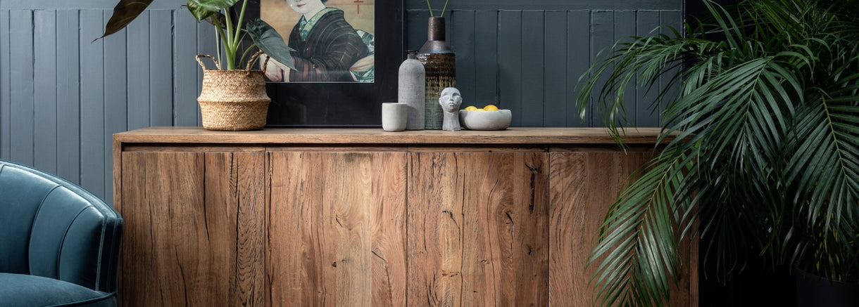 A view of the top of the Knightsbridge Large Reclaimed Oak Sideboard with plants, ornaments and art.