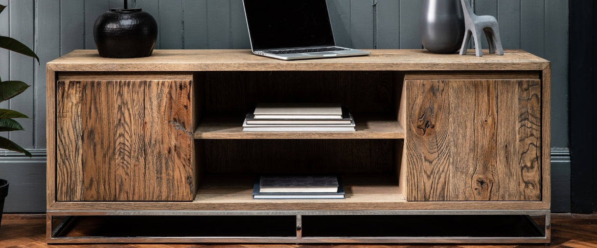 Books utilise the shelving space of the Knightsbridge Large Reclaimed Oak TV Unit whilst a laptop and ornaments take pride of place on top.