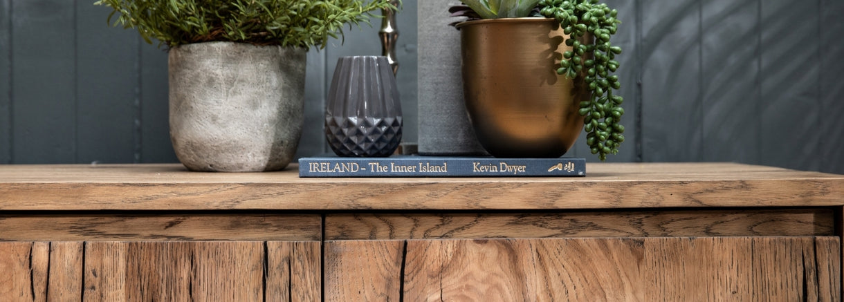 A book and plants sit atop the Knightsbridge Small Reclaimed Oak Sideboard