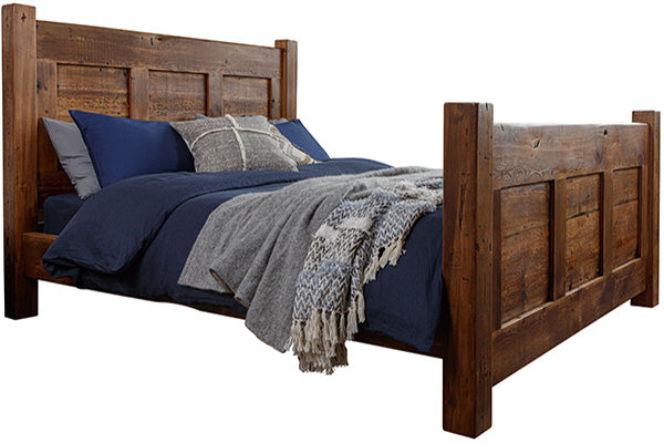 A reclaimed wood bed in a dark finish with navy blue bedsheets