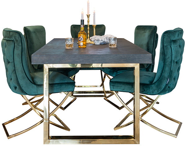 Glamorous dining table made of reclaimed wood and a gold frame. Forest green velvet dining chairs and decorative items.