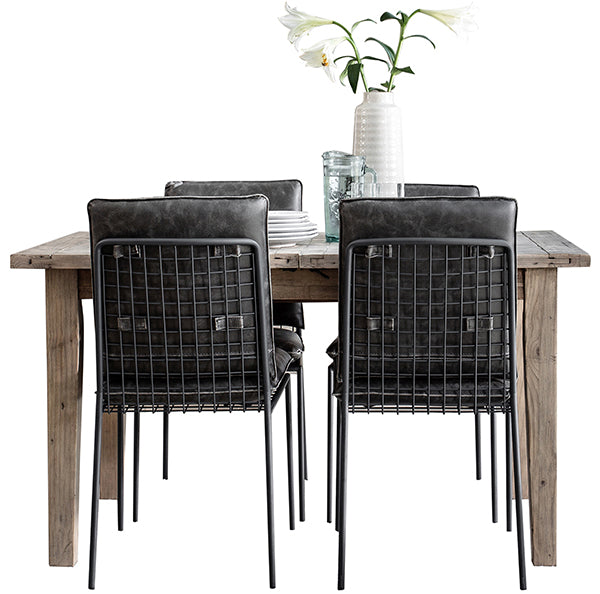 Reclaimed wood dining table in light grey wash with industrial style dining chairs and a vase with flowers