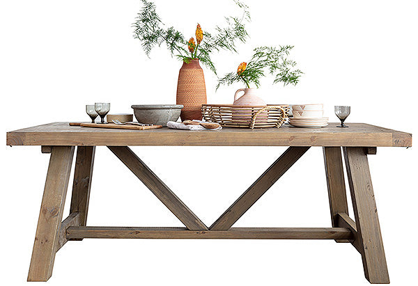 Light farmhouse style trestle dining table with linen and greenery