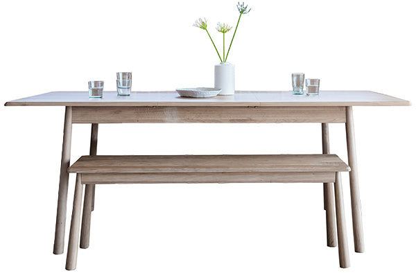 Sleek and Scandi wooden dining table with a light reclaimed wood bench and a vase with flowers