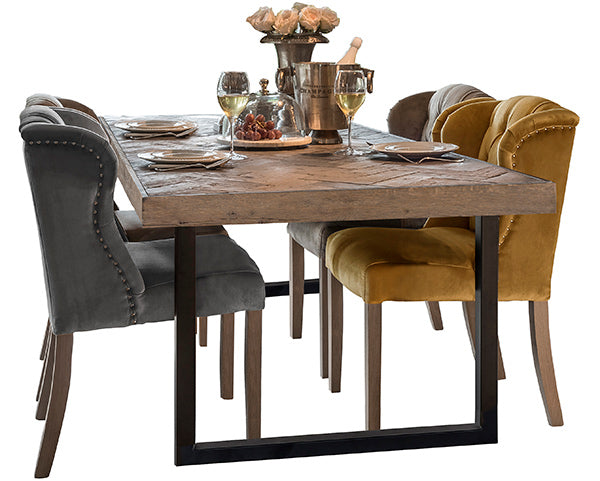 Luxurious wooden dining table on steel legs with colourful upholstered chairs