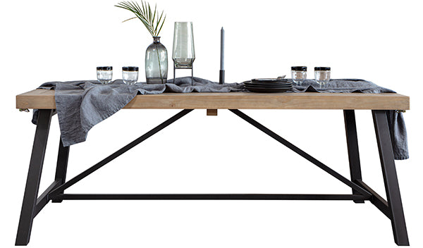 Industrial and wooden dining table with linen, greenery and pottery on top