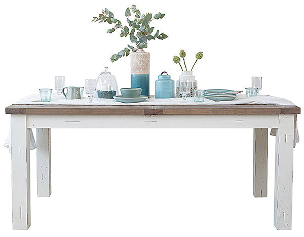 Farmhouse style dining table in distressed white finish and a medium brown rim. Plants and pottery on top of the table