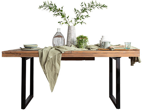 Industrial style reclaimed wood table on black steel legs with greenery, ceramics and linen on top