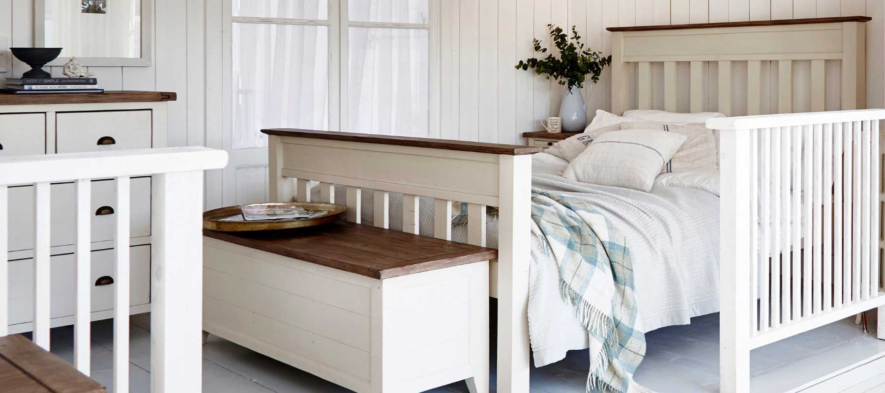 White blanket box and white wooden bed