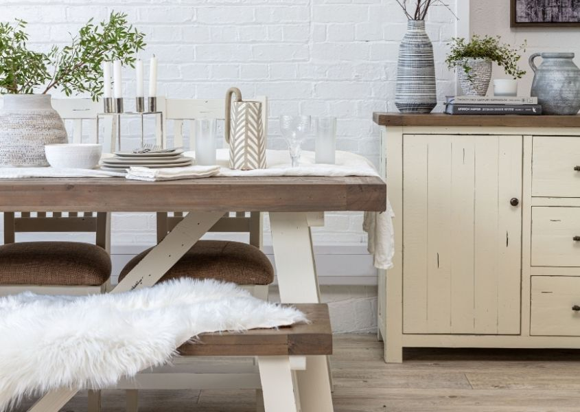 Reclaimed wood dining table with white painted legs and white painted wooden sideboard in background