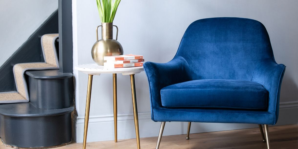 Blue velvet armchair with side table and grey painted stairs