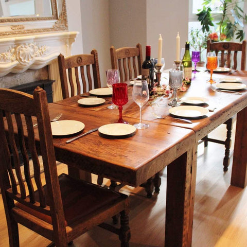Red table decorations on farmhouse reclaimed wood extending dining table