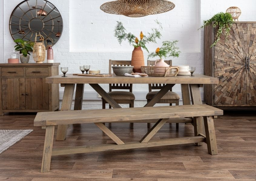 Reclaimed wood dining table decorate with terracotta vase and wooden sideboards in background