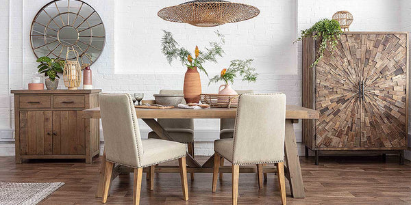 Earthy dining room with a reclaimed table, upholstered cream chairs, textured cabinet and an industrial sideboard