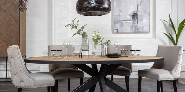 Luxe dining room with light grey button back dining chairs, spider leg industrial dining table, black rattan pendant and tableware