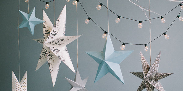 Several hanging paper stars with a string of lights