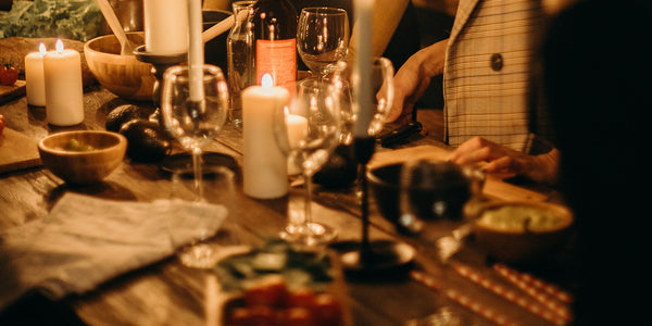 People huddled around a rustic dining table with lit candles, drinks and food