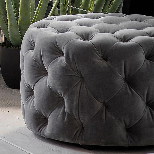 Grey buttoned footstool in soft velvet fabric