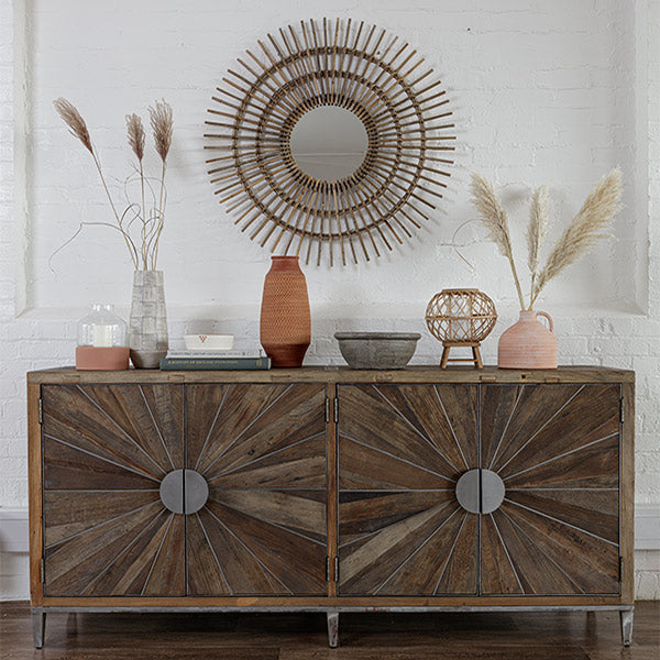 Rustic and industrial large sideboard with round metal handles, earthy decorative items on top and a bohemian sunburst mirror