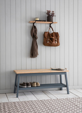 Grey hallway bench with shoes underneath
