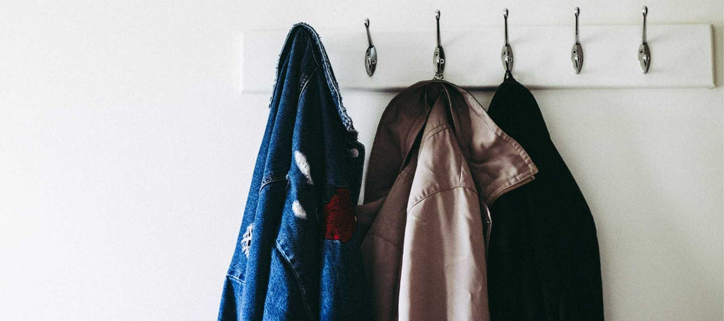 Denim jacket and other coats hanging on row of hooks