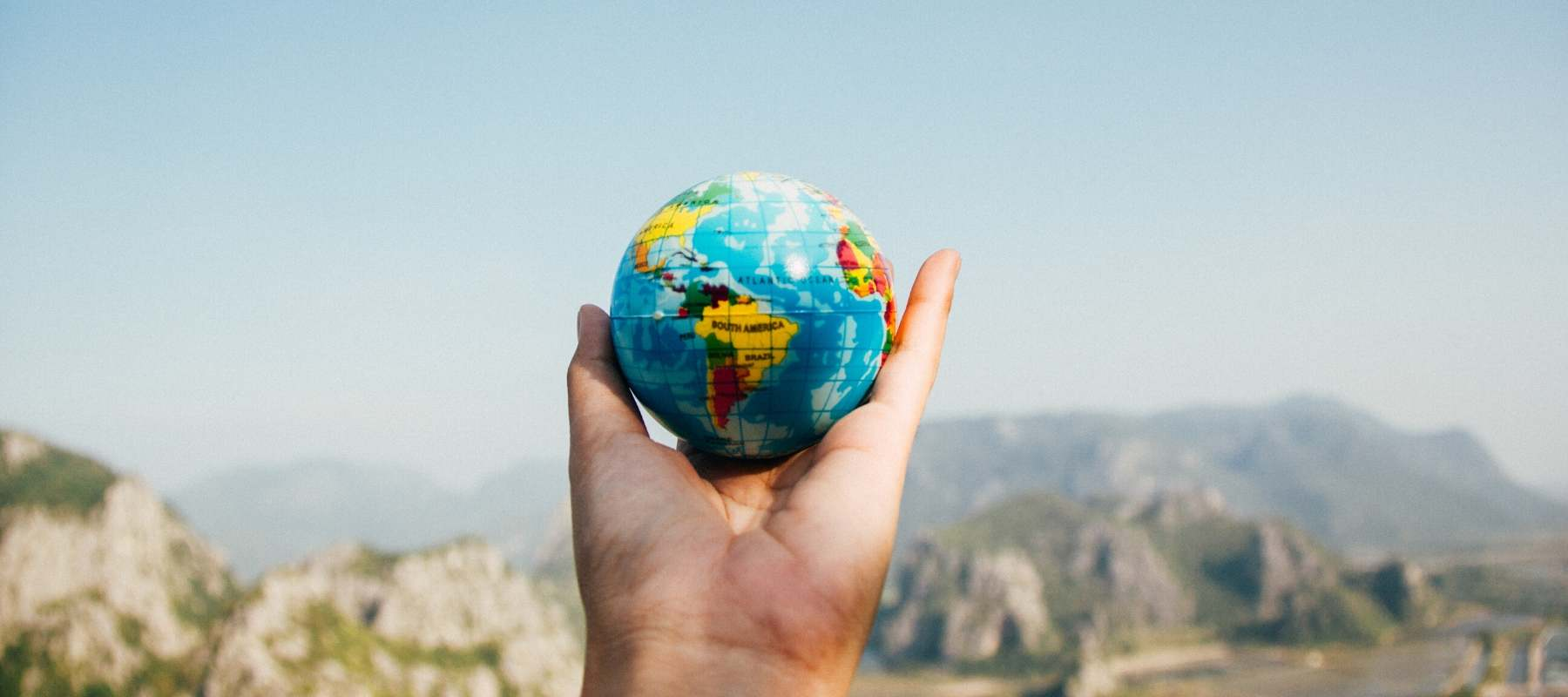 Hand holding a globe of the world against a blue sky