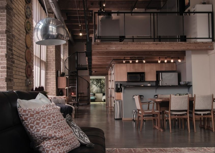 Open plan industrial living space with exposed brick walls and wooden dining table