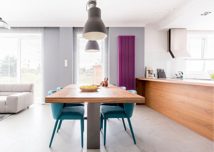 Open plan kitchen/diner with tall bright pink radiator and industrial dining table with green fabric dining chairs
