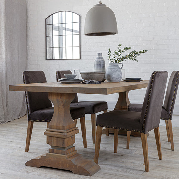 Reclaimed oak dining table with grey finish and dark grey velvet dining chairs, a curved window mirror and a grey pendant light