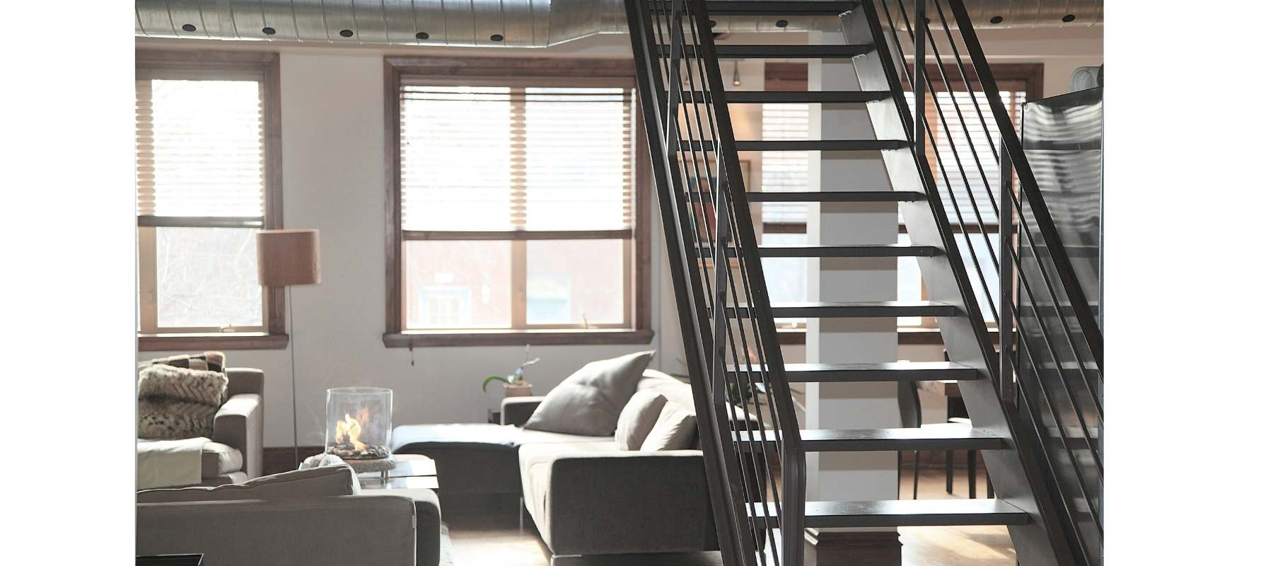 Loft style apartment with metal stairs and large windows