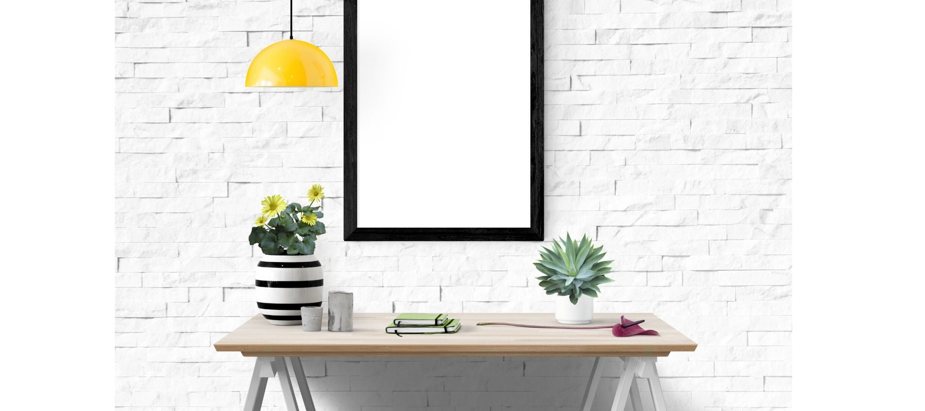 Black framed mirror on white brick wall with yellow hanging light