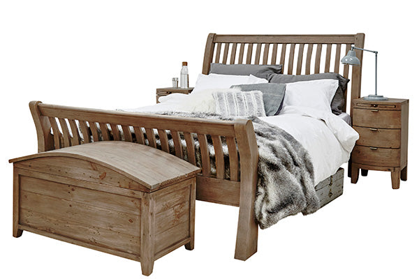 Reclaimed wood bed with white bed sheets and a wooden blanket box and bedside table