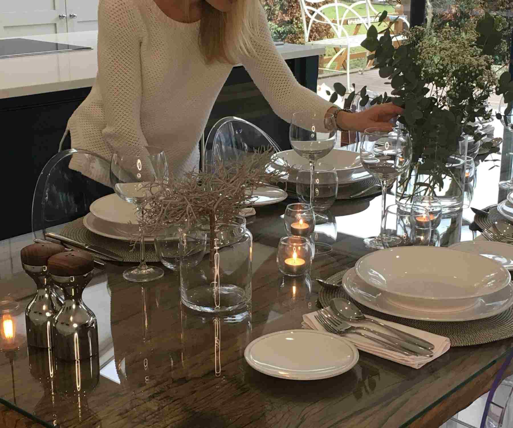 Lady in white jumper laying reclaimed wood dining table